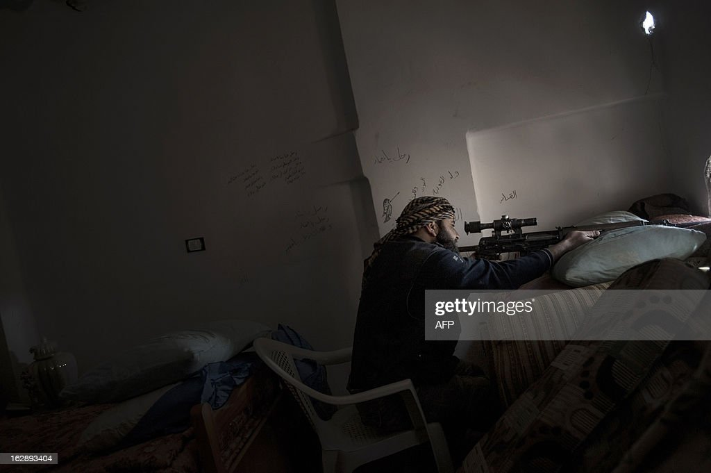 A Rebel sniper takes aim at government forces with his Dragunov SVD rifle from a house in the Syrian eastern city of Deir Ezzor, on February 28, 2013. The United States said it would for the first time provide direct aid to Syrian rebels, but not the arms they had hoped for, as well as $60 million in extra assistance to the political opposition. AFP PHOTO/ZAC BAILLIE