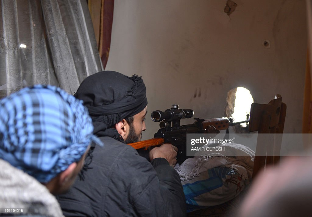 A rebel sniper takes aim at pro-government forces through a hole in the Old City of Syria's northern city of Aleppo on February 9, 2013. President Bashar al-Assad reshuffled his cabinet as regime warplanes raided rebel areas in a bid to end the stalemate in Syria's deadly civil war and hopes for a political solution appeared to founder.