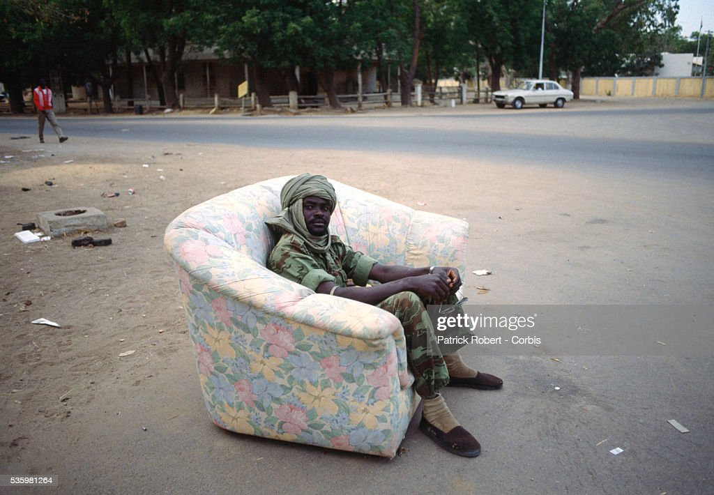A rebel soldier with the Forces Armees Nationales Chadiennes (FANT), or National Army of Chad, rests on a sofa in the streets of N'Djamena. Lead by Chadian Chief of Staff Idriss Deby, the FANT rebellion seized power from head of state Hissen Habre in a French- and Libyan-backed military coup. Deby later won the first multi-party Chadian presidential vote in 1996.