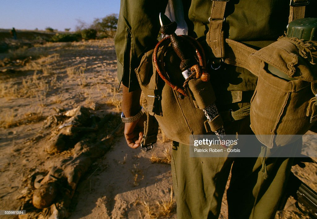 A rebel soldier with the Forces Armees Nationales Chadiennes (FANT), or National Army of Chad, walks past the corpse of a Chadian civilian following the fighting between Idriss Deby's partisans and Hissen Habre's troops. Lead by Deby, the Chadian Chief of Staff, the FANT rebellion seized power from head of state Hissen Habre in a French- and Libyan-backed military coup. Deby later won the first multi-party Chadian presidential vote in 1996.