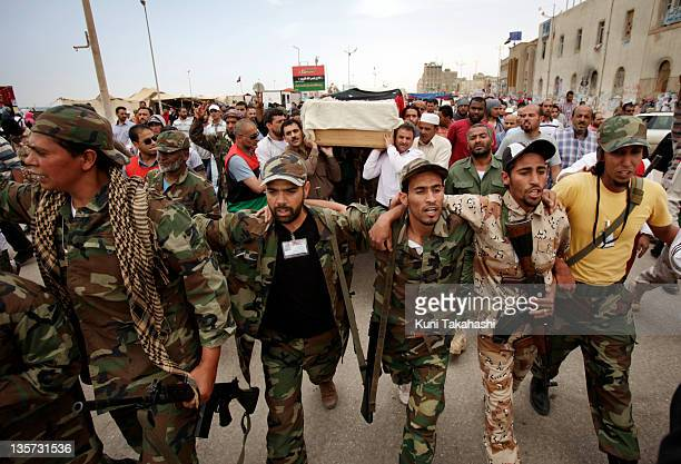 Rebel soldiers and mourners carry the casket of Ahmed Lagha May 23 2011 in Benghazi Libya Lagha a rebel soldier was killed during a fight near...