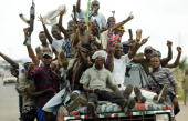 Rebel soldiers from Liberia's main rebel faction Liberians United for Reconciliation and Development sit in the back of a pickup truck cheering a...