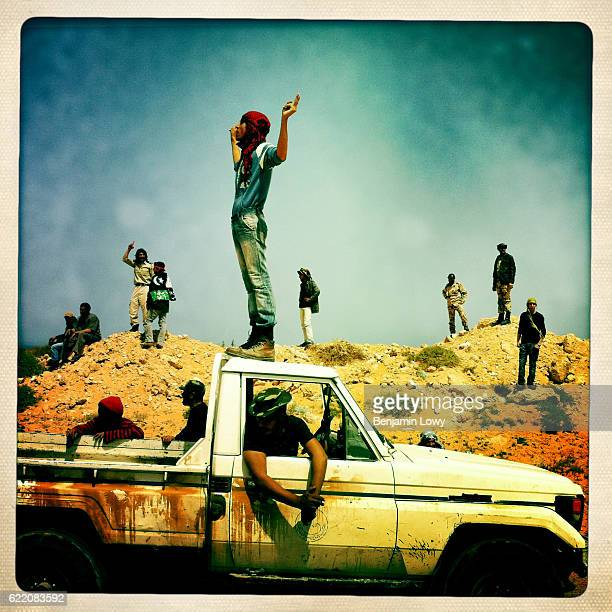 Rebel soldiers try to rally their comrades with a cry of 'Allah Akbar' following a massive retreat in the face of relentless mortar attacks on March...