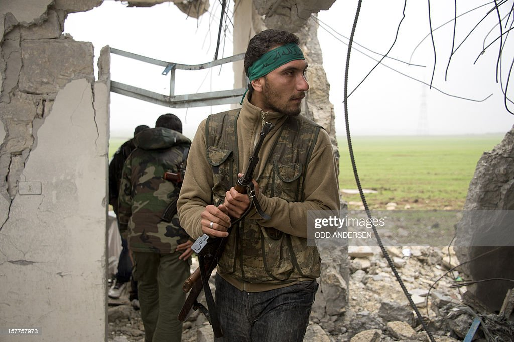 Rebel soldiers walk through the rubble of building in the northern Syrian city Aleppo on December 6, 2012. Fighting erupted in the Aleppo district of Bustan al-Basha as troops advanced for the first time into the stronghold of Islamist militants, a military source and resident told AFP.