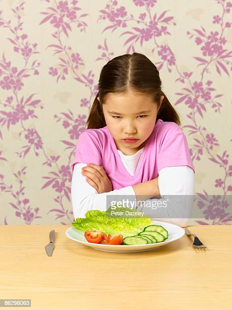 Rebellious child refusing to eat salad.