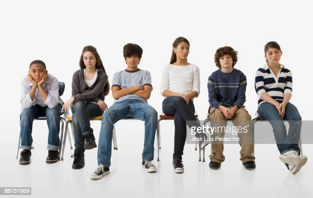 Rebellious teenagers sitting in chairs