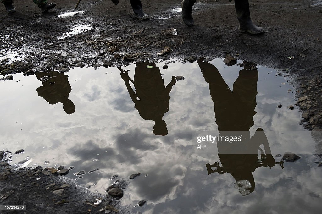 M23 rebels are reflected in a puddle as they withdraw through Sake having left their positions in the hills north of the town in the east of the Democratic Republic of Congo, on November 30, 2012. Hundreds of Congolese rebels withdrew on November 30 from frontline positions around Goma as promised under a regionally brokered deal, while police entered the key eastern city to take over control.