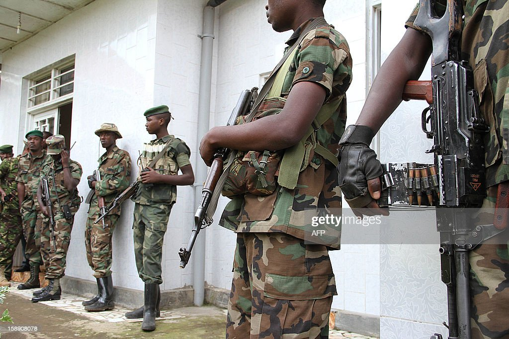 M23 rebels army keep security during a press conference at Bunagana on January 3, 2013. The M23 rebel group wants the Kinshasa government to first sign cease fire agreement before the second rounds of talks resume in Kampala tomorrow or else they will recall the delegation sent to Kampala for the peace talks.
