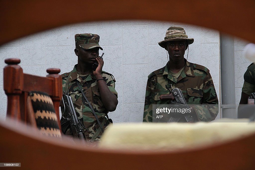 M23 rebels' army keep security during a press conference in Bunagana, on January 3, 2013. The M23 rebel group wants the Kinshasa government to first sign cease fire agreement before the second rounds of talks resume in Kampala tomorrow, or else they will recall the delegation sent to Kampala for the peace talks.