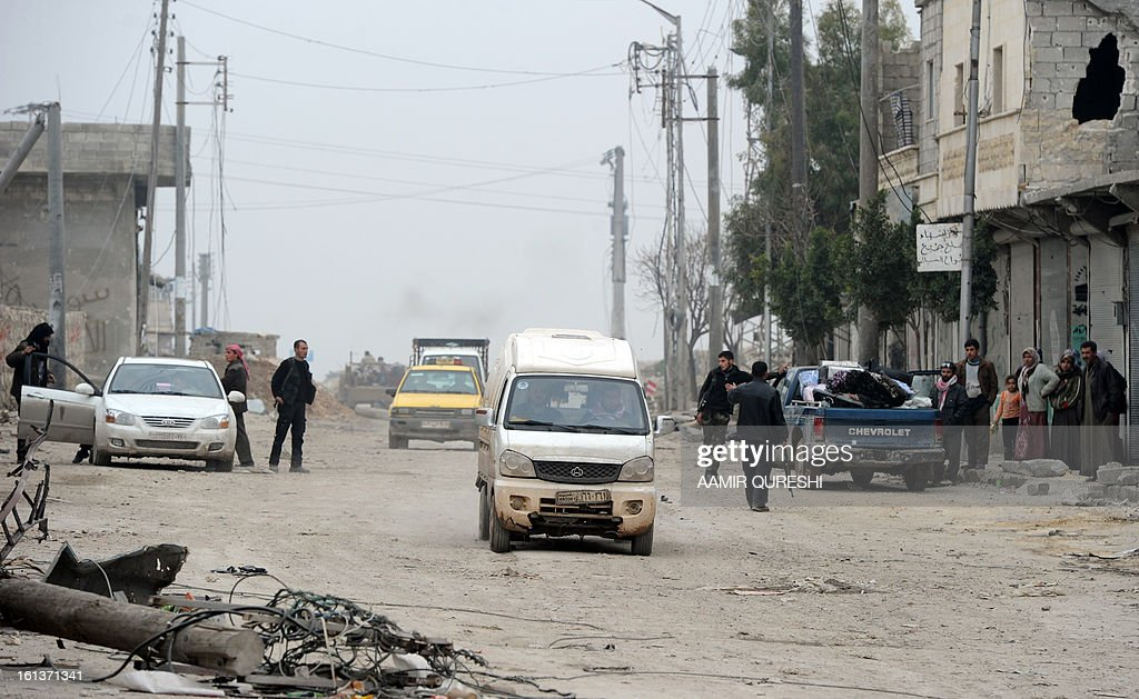 Rebels check Syrian civilians at a check point as they flee the violence in the Sheikh Said district of the northern city of Aleppo on February 10, 2013. Syrian rebels launched fierce assaults on regime troops in several parts of the country, including near Deir Ezzor where they used tanks to shell an army brigade, a watchdog and activists said. AFP PHOTO/AAMIR QURESHI