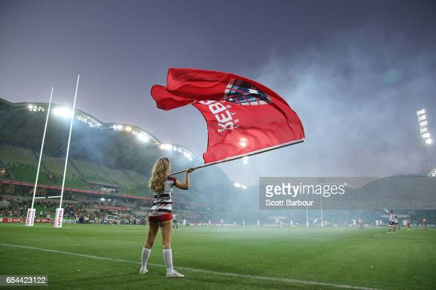 Rebels cheerleader waves a giant Rebels flag as the Rebels run onto the field during the round four Super Rugby match between the Rebels and the...