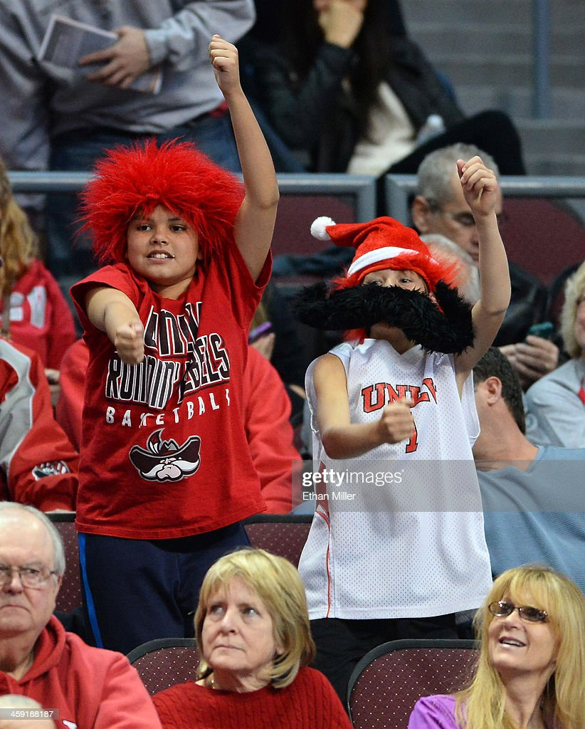 Rebels fans Travis Haight (L) and Brock Forte, both 10 and from Nevada, dance in the stands during the UNLV's game against the Mississippi State Bulldogs in the 2013 Continental Tire Las Vegas Classic at the Orleans Arena on December 23, 2013 in Las Vegas, Nevada.