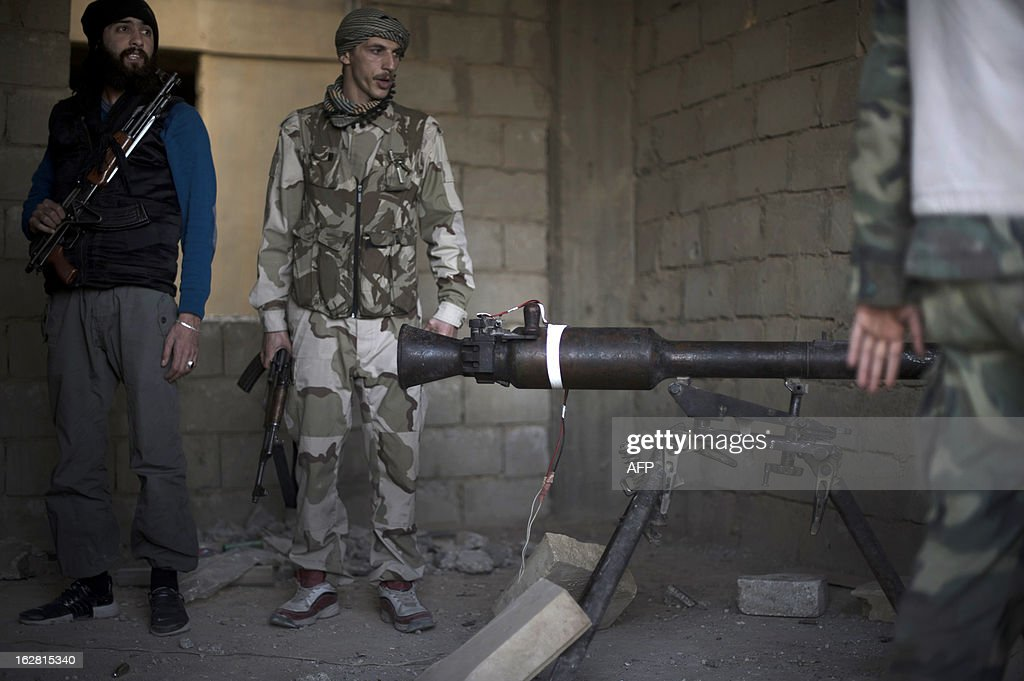 Rebels fighters prepare to fire a portable canon against an adjacent Syrian government-held building during fighting on February 27, 2013 in the Hawiqah neighbourhood of the eastern Syrian town of Deir Ezzor. Syria's opposition and foreign powers hold crucial talks in Rome with Washington suggesting it is ready to boost support to rebels in their struggle against President Bashar al-Assad. AFP PHOTO/ZAC BAILLIE