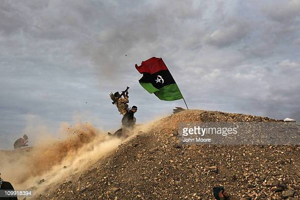 Rebels fire a rocketpropelled grenade at a Libyan air force fighter jet on March 10 2011 in Ras Lanuf Libya Most rebel forces fled the city as...