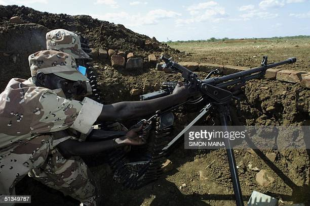Rebels from the Sudan People Liberation Army assemble a machine gun 11 June 2002 left behind by the government troops after they fled the southern...
