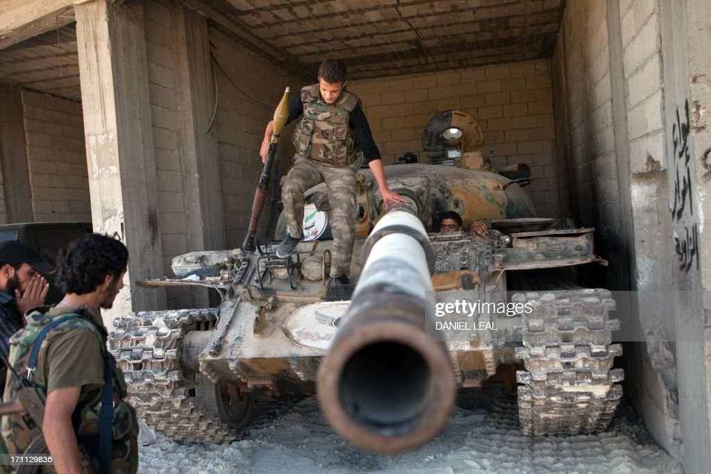 Rebels inspect a T-72 tank parked in a secret location close to the village of Al-Rami, near the town of Ariha, in the northwestern Syrian province of Idlib, on June 22, 2013. World powers supporting Syria's rebels decided to take 'secret steps' to change the balance on the battlefield, after the United States and others called for increasing military aid to insurgents.