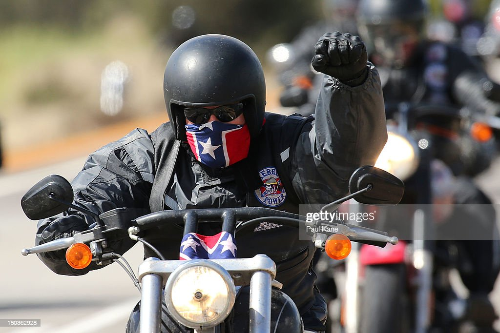 A Rebels motorcycle club member salutes as he rides from Meckering to the Perth CBD on September 12, 2013 in Perth, Australia. An estimated 1000 Rebels from chapters all over Australia gather for the road trip across the country to Perth.
