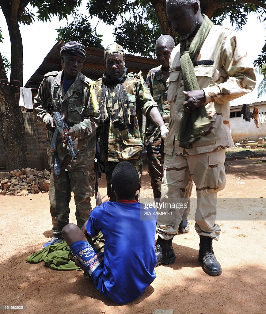 Rebels of the Seleka coalition arrest a man claiming to also belong to the Seleka movement, suspected of looting a house in a popular neighbourood of Bangui on March 26, 2013. Central African Republic strongman Michel Djotodia was set to unveil a new government on March 26 after declaring he would rule by decree following the latest coup in the notoriously unstable nation. Looters were on the rampage in the capital Bangui after Djotodia's Seleka rebel coalition seized control in a rapid-fire weekend assault that forced president Francois Bozize into exile and was condemned by the international community.