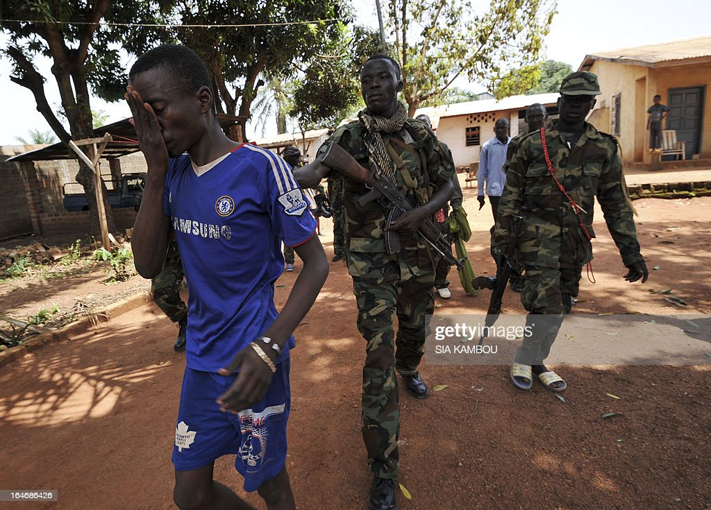 Rebels of the Seleka coalition arrest a man, claiming to belong to the Seleka movement, suspected of looting a house in a popular neighbourood of Bangui on March 26, 2013. Central African Republic strongman Michel Djotodia was set to unveil a new government on March 26 after declaring he would rule by decree following the latest coup in the notoriously unstable nation. Looters were on the rampage in the capital Bangui after Djotodia's Seleka rebel coalition seized control in a rapid-fire weekend assault that forced president Francois Bozize into exile and was condemned by the international community. AFP PHOTO / SIA KAMBOU