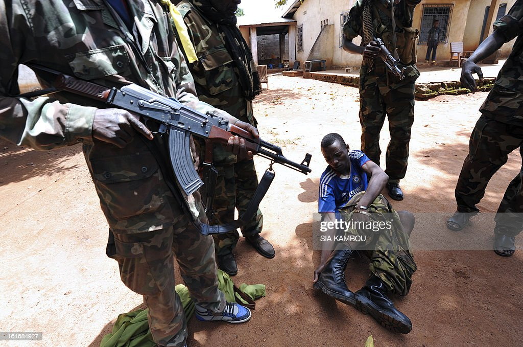 Rebels of the Seleka coalition arrest a man wearing military fatigue, claiming to also belong to the Seleka movement, suspected of looting a house in a popular neighbourood of Bangui on March 26, 2013. Central African Republic strongman Michel Djotodia was set to unveil a new government on March 26 after declaring he would rule by decree following the latest coup in the notoriously unstable nation. Looters were on the rampage in the capital Bangui after Djotodia's Seleka rebel coalition seized control in a rapid-fire weekend assault that forced president Francois Bozize into exile and was condemned by the international community.