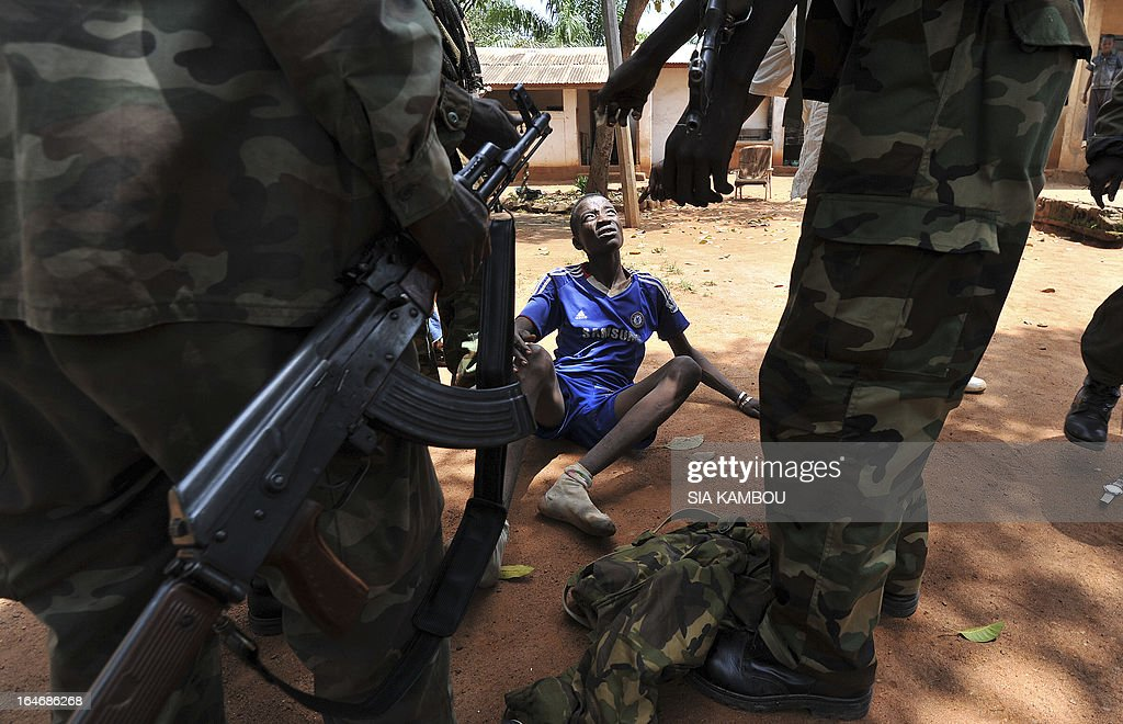 Rebels of the Seleka coalition arrest a man, who was wearing a military fatigue and claiming to belong to the Seleka movement, suspected of looting a house in a popular neighbourood of Bangui on March 26, 2013. Central African Republic strongman Michel Djotodia was set to unveil a new government on March 26 after declaring he would rule by decree following the latest coup in the notoriously unstable nation. Looters were on the rampage in the capital Bangui after Djotodia's Seleka rebel coalition seized control in a rapid-fire weekend assault that forced president Francois Bozize into exile and was condemned by the international community.
