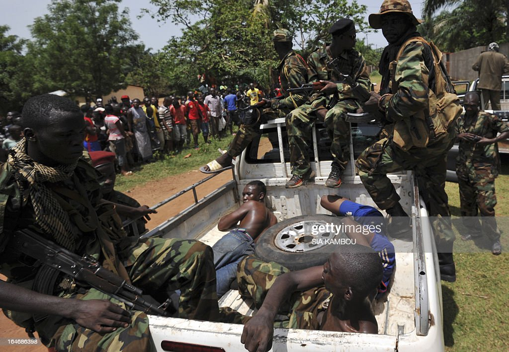 Rebels of the Seleka coalition escort in a pick up truck men, claiming to belong to the Seleka movement, suspected of looting a house in a popular neighbourood of Bangui on March 26, 2013. Central African Republic strongman Michel Djotodia was set to unveil a new government on March 26 after declaring he would rule by decree following the latest coup in the notoriously unstable nation. Looters were on the rampage in the capital Bangui after Djotodia's Seleka rebel coalition seized control in a rapid-fire weekend assault that forced president Francois Bozize into exile and was condemned by the international community. AFP PHOTO / SIA KAMBOU