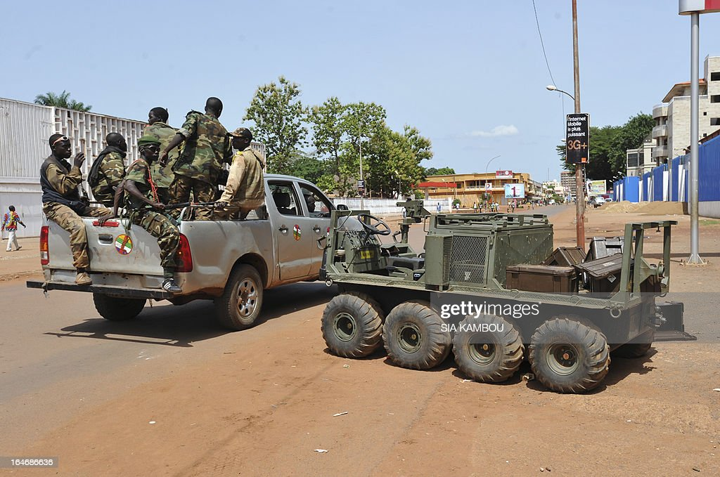 Rebels of the Seleka coalition on a pick up truck drive past an abandonned South African vehicle in Bangui on March 26, 2013. Central African Republic strongman Michel Djotodia was set to unveil a new government on March 26 after declaring he would rule by decree following the latest coup in the notoriously unstable nation. Looters were on the rampage in the capital Bangui after Djotodia's Seleka rebel coalition seized control in a rapid-fire weekend assault that forced president Francois Bozize into exile and was condemned by the international community.