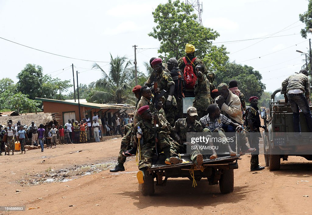 Rebels of the Seleka coalition sit on a pick up truck as they search for people suspected of looting in a neighbourood of Bangui on March 26, 2013. Central African Republic strongman Michel Djotodia was set to unveil a new government on March 26 after declaring he would rule by decree following the latest coup in the notoriously unstable nation. Looters were on the rampage in the capital Bangui after Djotodia's Seleka rebel coalition seized control in a rapid-fire weekend assault that forced president Francois Bozize into exile and was condemned by the international community. AFP PHOTO / SIA KAMBOU