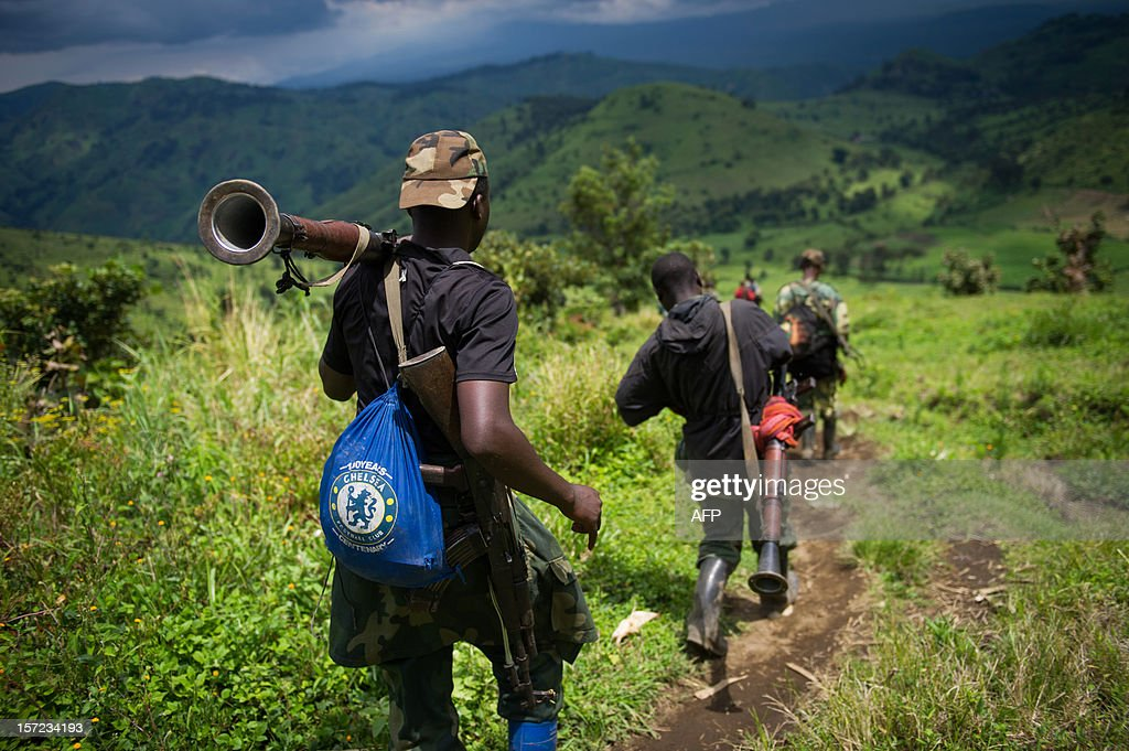M23 rebels withdraw through the hills having left their position in the village of Karuba, eastern Democratic Republic of Congo, on November 30, 2012. Hundreds of Congolese rebels withdrew on November 30 from frontline positions around Goma as promised under a regionally brokered deal, while police entered the key eastern city to take over control.