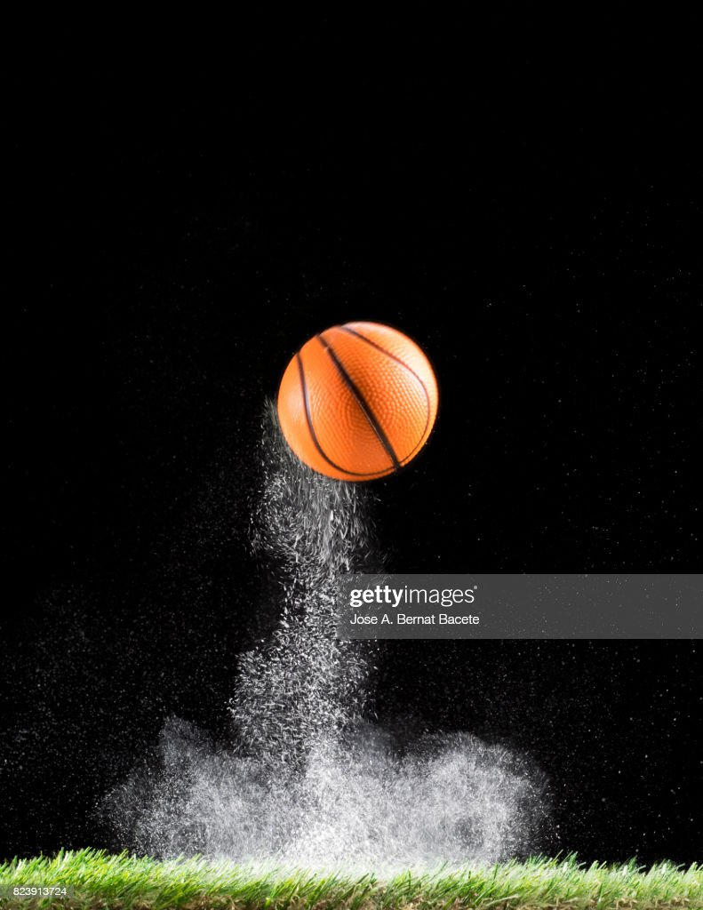 Rebound of a ball of basketball for the impact on a surface of lawn, of an field of game, with ascending powder : Stock Photo