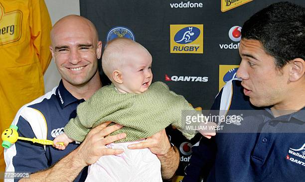 Recalled after sixyear absence Australian player Sam Cordingley passes a crying baby to teammate Mark Gerrard in Melbourne 14 June 2006 as...