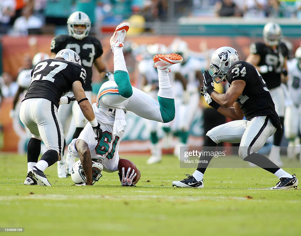 receiver Brandon Marshall #19 (C) of the Miami Dolphins makes a catch against Safety's Matt Giordano #27 and Michael Huff #24 of the Oakland Raiders at Sun Life Stadium on December 4, 2011 in Miami Gardens, Florida.