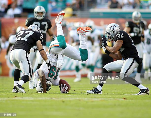 receiver Brandon Marshall of the Miami Dolphins makes a catch against Safety's Matt Giordano and Michael Huff of the Oakland Raiders at Sun Life...