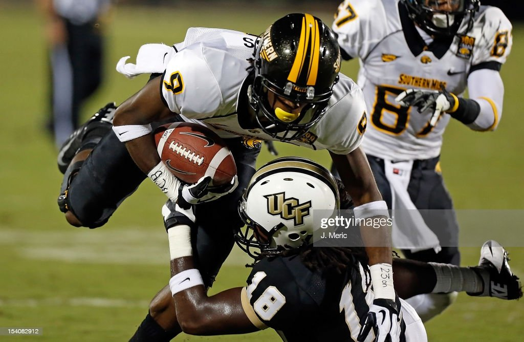 Receiver Chris Briggs #9 of the Southern Mississippi Golden Eagles is tackled by defender Kemal Ishmael #18 of the Central Florida Knights during the game at Bright House Networks Stadium on October 13, 2012 in Orlando, Florida.