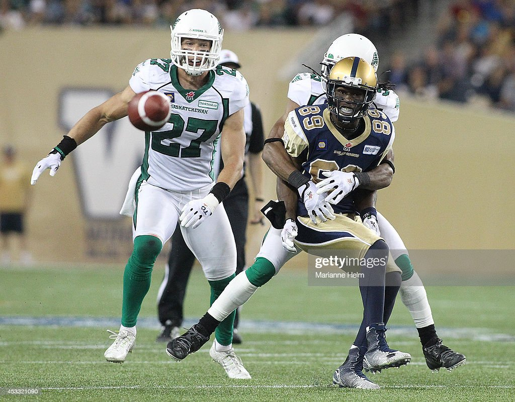 Receiver Clarence Denmark #89 of the Winnipeg Blue Bombers awaits the ball as he is held during action against the Saskatchewan Roughriders looks on in second half action in a CFL game at Investors Group Field on August 7, 2014 in Winnipeg, Manitoba, Canada.