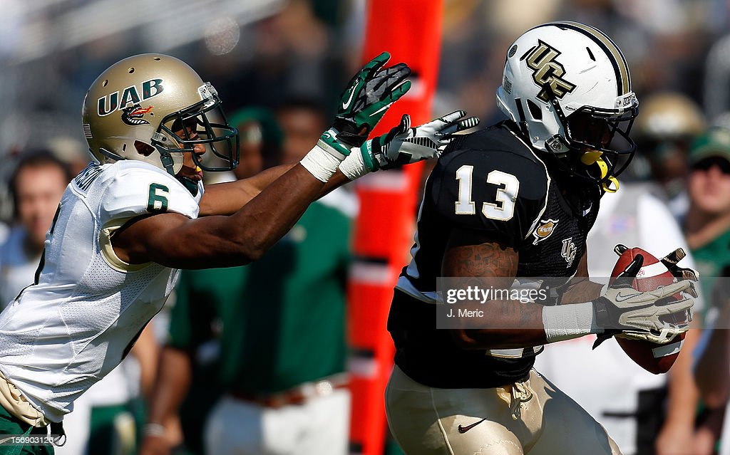 Receiver Dontravius Floyd #13 of the Central Florida Knights catches a pass in front of defender Lamar Johnson #6 of the Alabama Birmingham Blazers during the game at Bright House Networks Stadium on November 24, 2012 in Orlando, Florida.