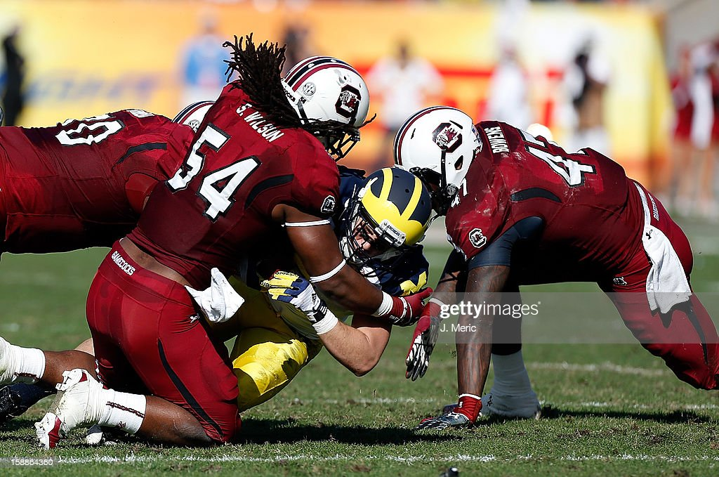 Receiver Drew Dileo #9 of the Michigan Wolverines gets a first down on a fake punt as defenders Chaz Sutton #90, Shaq Wilson #54 and Reginald Bowers #47 of the South Carolina Gamecocks close in for the tackle during the Outback Bowl Game at Raymond James Stadium on January 1, 2013 in Tampa, Florida.