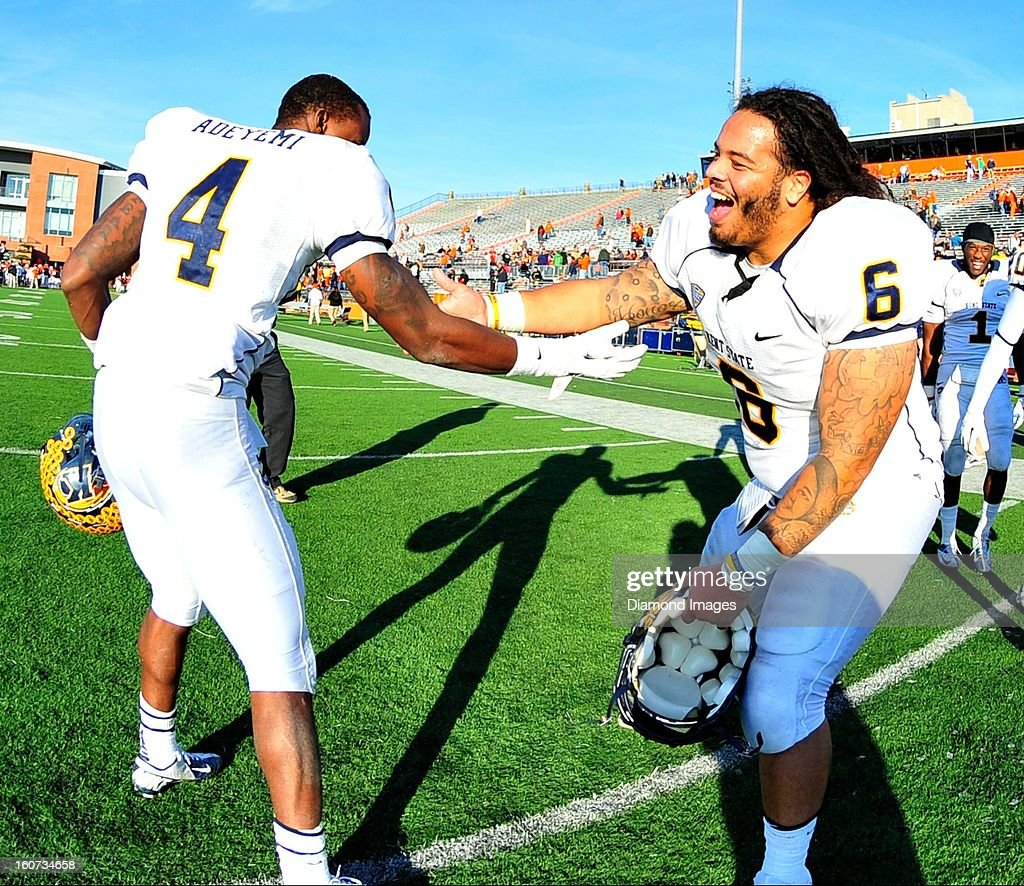Receiver Eric Adeyemi #4 and defensive linemen Dana Brown Jr. #6 of the Kent State Golden Flashes celebrate after a game with the Bowling Green Falcons at Dolt L. Perry Stadium in Bowling Green, Ohio. The Kent State Golden Flashes won 31-24.