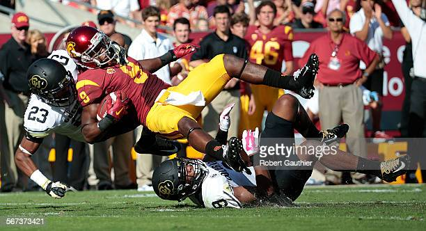 LOS ANGELES CA OCTOBER 18 2014 USC receiver Juju Smith is brought down by Colorado defensive players Tedrik Thompson and Ahkello Witherspoon during a...