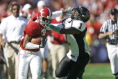 Receiver Keith Brown of the Alabama Crimson Tide stiffarms Vincent Meeks of Texas Tech during a 1310 victory over the Red Raiders at the ATT Cotton...