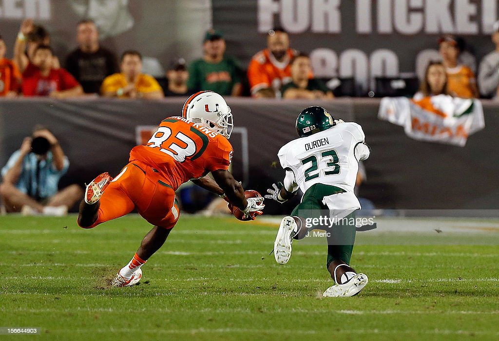 Receiver Kendal Thompkins #83 of the Miami Hurricanes makes a catch in front of defender Kenneth Durden #23 of the South Florida Bulls during the game at Sun Life Stadium on November 17, 2012 in Miami Gardens, Florida.
