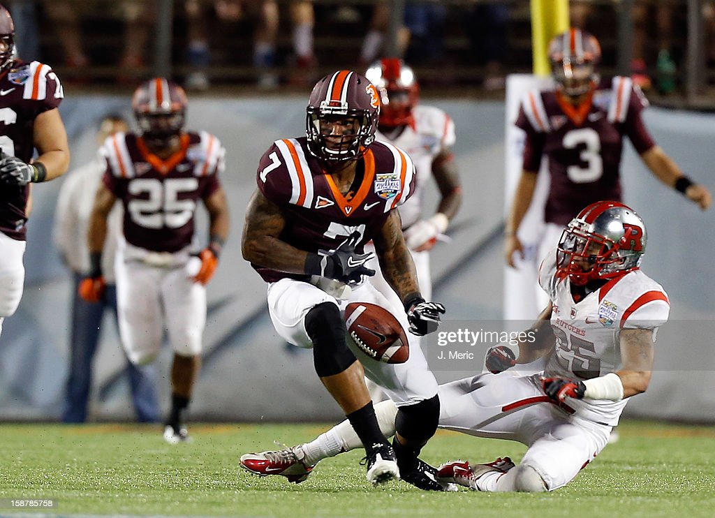 Receiver Marcus Davis #7 of the Virginia Tech Hokies fumbles after defender <a gi-track='captionPersonalityLinkClicked' href=/galleries/search?phrase=Brandon+Jones+-+American+Football+Cornerback&family=editorial&specificpeople=13463219 ng-click='$event.stopPropagation()'>Brandon Jones</a> #25 of the Rutgers Scarlet Knights hits him during the Russell Athletic Bowl Game at the Florida Citrus Bowl on December 28, 2012 in Orlando, Florida.