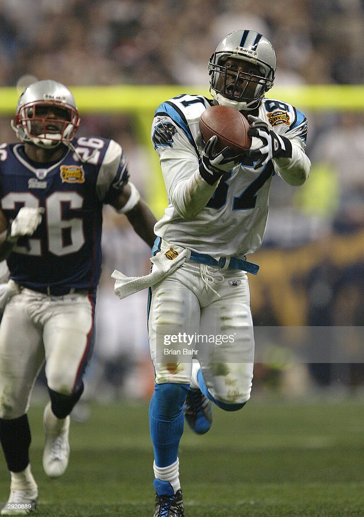 Receiver Muhsin Muhammad #87 of the Carolina Panthers catches an 85 yard touchdown pass in front of defensive back Eugene Wilson #26 of the New England Patriots in the fourth quarter of Super Bowl XXXVIII at Reliant Stadium on February 1, 2004 in Houston, Texas.