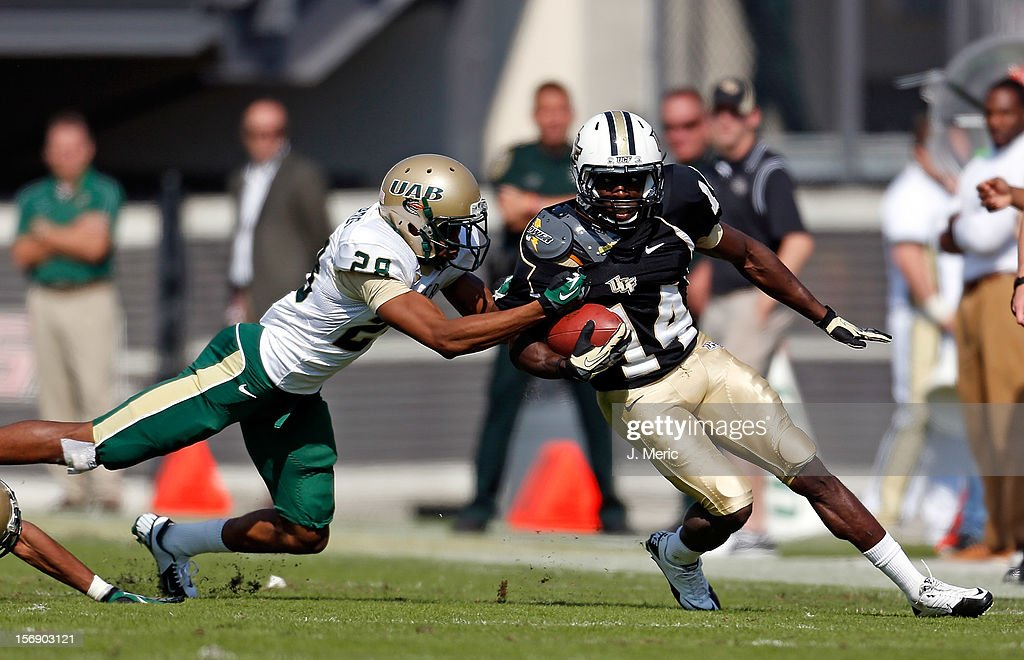 Receiver Quincy McDuffie #14 of the Central Florida Knights is tackled by defender Cornelius Richards #28 of the Alabama Birmingham Blazers during the game at Bright House Networks Stadium on November 24, 2012 in Orlando, Florida.
