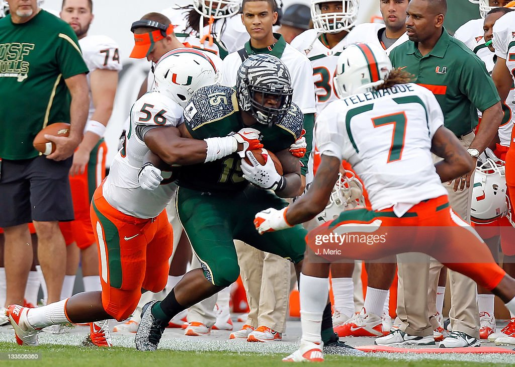 receiver Victor Marc #15 of the South Florida Bulls is tackled by defender <a gi-track='captionPersonalityLinkClicked' href=/galleries/search?phrase=Marcus+Robinson&family=editorial&specificpeople=215475 ng-click='$event.stopPropagation()'>Marcus Robinson</a> #56 of the Miami Hurricanes during the game at Raymond James Stadium on November 19, 2011 in Tampa, Florida.