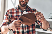 Close up of young man opening envelope and smiling while standing indoors