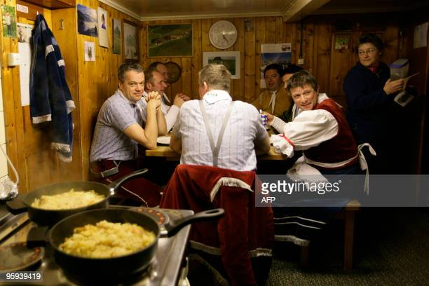 Recent picture of members of a 'Schuppel' eating breakfast at the beginning of the 'Silvesterchalusen' in Urnaesch in the Swiss canton Appenzell...