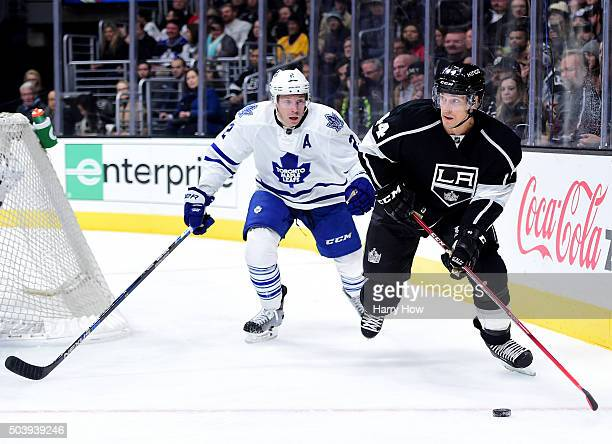Recently acquired player Vincent Lecavalier of the Los Angeles Kings looks to pass as he is chased by Matt Hunwick of the Toronto Maple Leafs during...