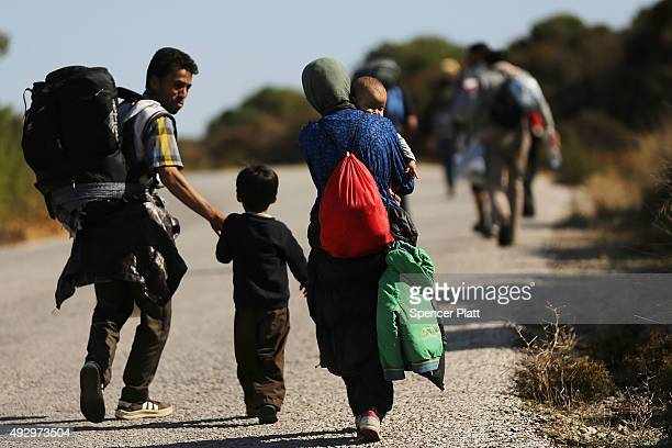 Recently arrived migrants make the long trip towards a reception center after arriving from Turkey onto the island of Lesbos on October 16 2015 in...