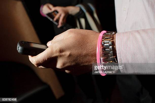 A recently laid off job seeker checks his smart phone at a'Wall Street Pink Slip Party' in New York The event was designed to connect the unemployed...